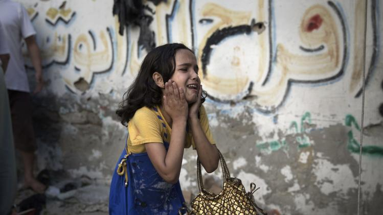 A Palestinian girl reacts at the scene of an explosion that medics said killed eight children and wounded 40 others at a public garden in Gaza City