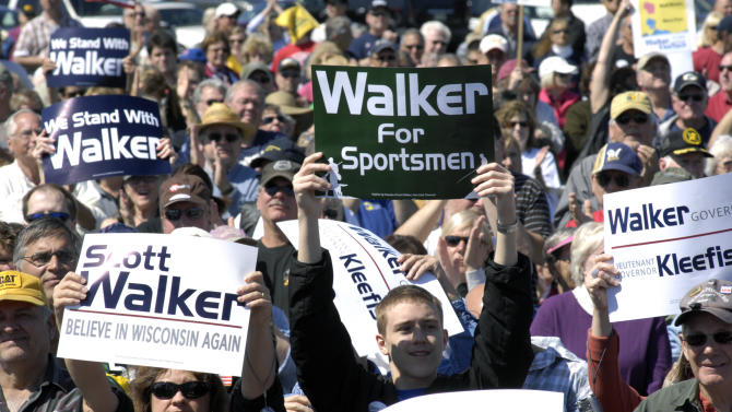Spectators hold up signs at a rally held by the Racine Tea Party PAC in Gorney Park in Caledonia, Wis. near Racine on Saturday, June 2, 2012. The rally was held in opposition to the Tuesday, June 5, recall election in which Democratic opponents are running against incumbents Gov. Scott Walker, Kleefisch and state Sen. Van Wanggaard of Racine. (AP Photo/Mark Hertzberg)