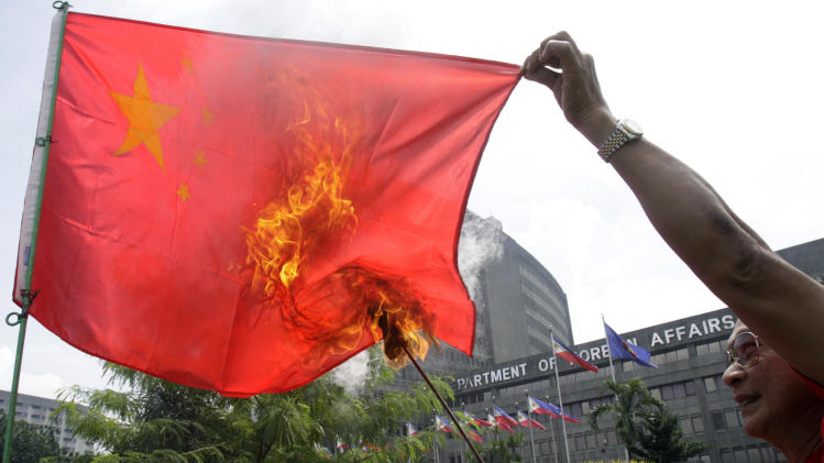 Former police officer Abner Afuang burns a Chinese flag in front of the Department of Foreign Affairs to oppose the presence of Chinese vessels in the disputed territory in the South China Sea Friday, July 27, 2012 in suburban Pasay City, south of Manila, Philippines. Afuang called on the government to persist on its claim on Scarborough Shoal which is within the country's economic zone. (AP Photo/Photo/Pat Roque)
