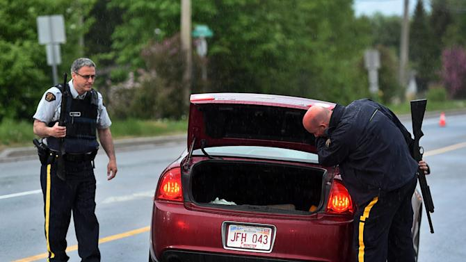 Police officers check a car at a roadblock in Moncton, New Brunswick, on Thursday, June 5, 2014. RCMP officers combed the streets and woods of this normally tranquil city Thursday in search of a man suspected of killing three officers in the deadliest attack on their ranks in nearly a decade. The suspect, 24-year-old Justin Bourque, was armed with high-powered long firearms. He was spotted three times while eluding the massive manhunt that emptied roads and kept families hunkered in their homes in Moncton, an east coast city where gun violence is rare. (AP Photo/The Canadian Press, Andrew Vaughan)
