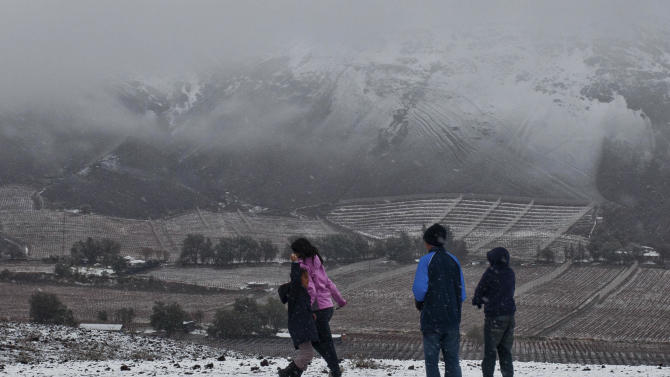 Children play during an unusual  snowfall in the Atacama desert, near Copiapo, Chile, Sunday, July 31, 2011. This has been the wettest winter in decades for Chile's arid northern desert, where fractions of an inch of rain have done major damage in some areas and set the stage for spectacular floral displays in the weeks to come. (AP Photo/Alex Fuentes)