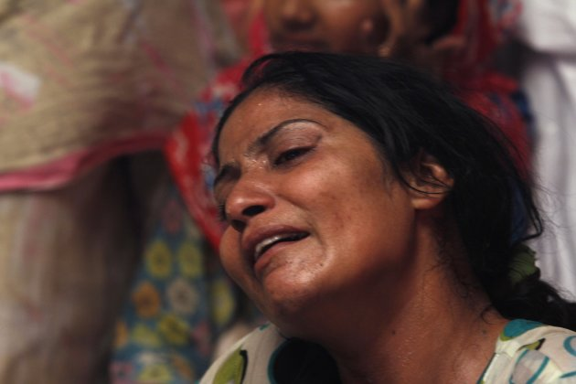 Mother of one of seventeen children who died after a gas cylinder exploded on a school bus, mourns near her child's casket on the outskirts of Gujrat