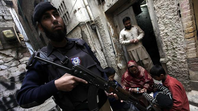 A member of the Pakistani security services stands guard while a health worker administers a polio vaccine to a child, in Peshawar, Pakistan, December 20, 2014. (EPA/ARSHAD ARBAB)
