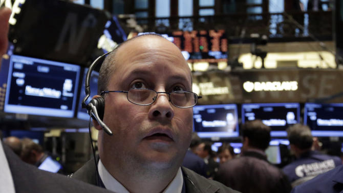 FILE - In this Oct. 31, 2013, file photo, Trader Jeffrey Vazquez works on the floor of the New York Stock Exchange. Stock futures are heading lower after U.S. policy makers said they would maintain a massive economic stimulus program. (AP Photo/Richard Drew, File)
