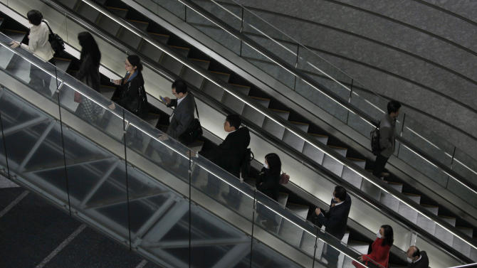 Commuters on escalators head to workplaces in Tokyo, Friday, March 29, 2013. Japan's jobless rate edged higher and industrial production fell slightly in February as consumer prices also fell, underscoring the fragility of the recovery of the world's third-largest economy. The government data released Friday showed the main consumer price index fell 0.3 percent from a year earlier as deflation continued to defy the combined efforts of the government and central bank to move toward a 2 percent inflation target. (AP Photo/Shuji Kajiyama)