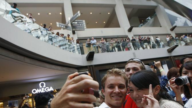 Mercedes Formula One drivers Nico Rosberg of Germany poses for photos after a publicity event to unveil watches that he co-designed in Singapore