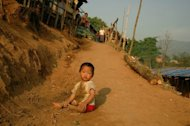 A Kachin child plays in a refugee camp on the border with China in May. China has pushed thousands of refugees from Myanmar&#39;s Kachin minority back across the border into a province wracked by fighting between government troops and ethnic guerillas, the rebels said Friday