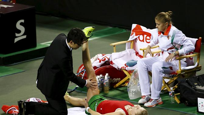 Govortsova of Belarus has her leg massaged during her FedCup tennis match against Kurumi Nara of Japan in Tokyo