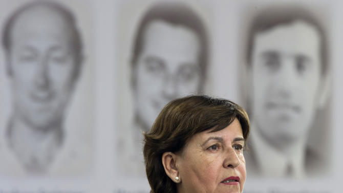Ankie Spitzer, widow of Israeli fencing trainer Andre Spitzer, delivers a speech in front of  photos of victims during a commemoration ceremony for the assassination victims of the Olympic games in Munich in 1972, at the former airbase in Fuerstenfeldbruck, southern Germany, Wednesday, Sept. 5, 2012. Relatives of Israelis slain by Palestinian gunmen during the games and survivors of the attack are marking its 40th anniversary with German politicians and Jewish leaders at the air base where most of the 12 victims died. Five terrorists were also killed in the failed liberation attempt. (AP Photo/dapd, Lennart Preiss)