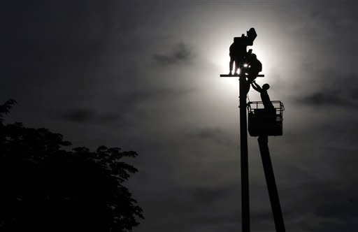 Filipino workers attach LED lights on a post at Manila's Rizal Park, Philippines on Thursday, July 12, 2012. The switch from regular bulb to LED on the park's 800 lampposts is part of the Department of Tourism's project to reduce the park's electric consumption by 50 percent and make it environment-friendly. (AP Photo/Aaron Favila)