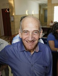 Former Israeli prime minister Ehud Olmert smiles at the District Court in Jerusalem. An Israeli court on Tuesday found Olmert guilty on one charge in a closely watched corruption case, but cleared him on two other charges, in a verdict he hailed as just