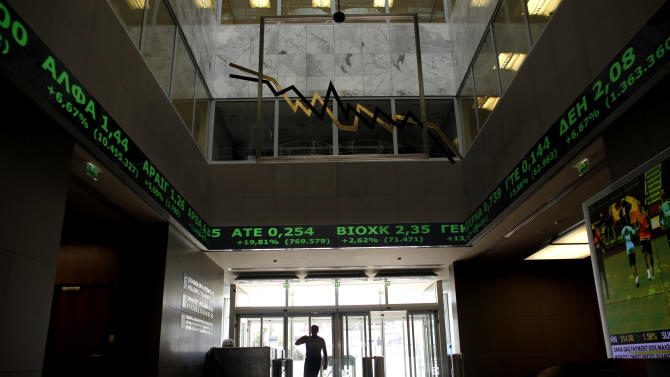 A man walks  as above  screens show rising stocks in green at the Greek Stock Exchange in Athens, on Monday , June 18, 2012. In Athens, stocks lost initial strong gains but were still 4.5 percent up in afternoon trading, on the back of strong gains last week that anticipated the conservative victory. (AP Photo/Kostas Tsironis)