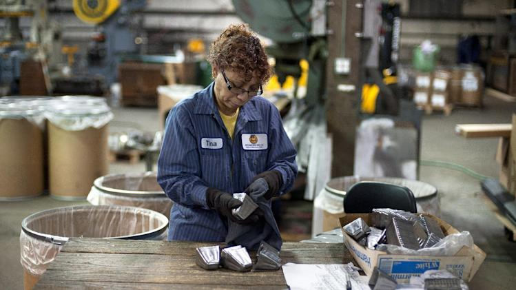 """Tina Veira cleans bells in a temporary site of the Bevin Bros. manufacturing in East Hampton, Conn., Wednesday, Oct. 3, 2012. The 180-year-old New England company that made the tiny bell that tinkles every time an angel gets its wings in the holiday classic """"It's a Wonderful Life"""" is resuming production months after the factory was destroyed in a fire. (AP Photo/Jessica Hill)"""
