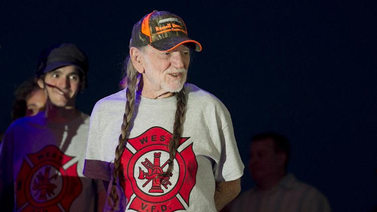 """Willie Nelson takes the stage wearing an """"I Support West VFD"""" T-shirt at his performance at The Backyard Live Oak Amphitheater in Austin, Texas, on Sunday, April 28, 2013. The concert was an early birthday celebration for Nelson, who turns 80 on Tuesday, and it was a benefit for the volunteer fire department in West, Texas, which is nearby where Nelson grew up in Abbott, Texas. A fertilizer plant exploded April 17 killing at least 14 people, including emergency responders, and hurting about 200 others. (AP Photo/Austin American-Statesman, Jay Janner) AUSTIN CHRONICLE OUT, COMMUNITY IMPACT OUT, MAGS OUT; NO SALES; INTERNET AND TV MUST CREDIT PHOTOGRAPHER AND STATESMAN.COM."""