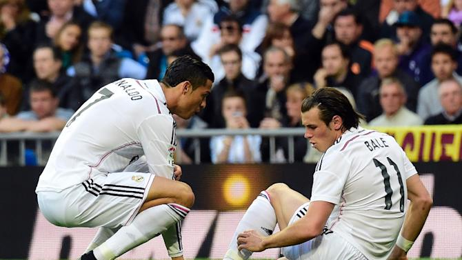 Real Madrid forward Gareth Bale (R) talks to teammate Cristiano Ronaldo after being injured during the Spanish La Liga match against Malaga FC in Madrid on April 18, 2015