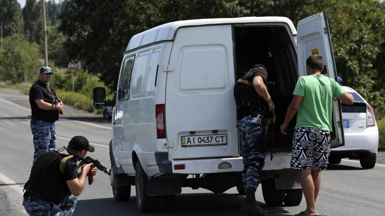 Armed pro-Russian separatists inspect a van as they stand guard on the suburbs of Shakhtarsk