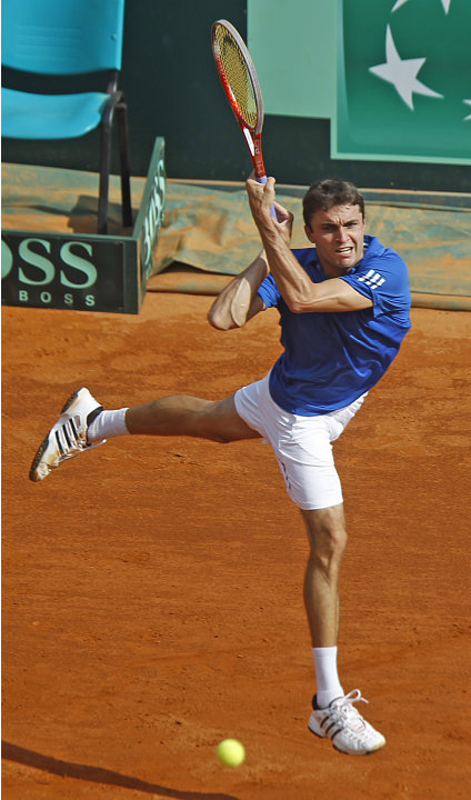 France's Gilles Simon returns the ball to U.S. team player John Isner during their match in the quarterfinal of the Davis Cup between France and U.S. in Monaco Friday April 6, 2012.(AP Photo/Remy de l