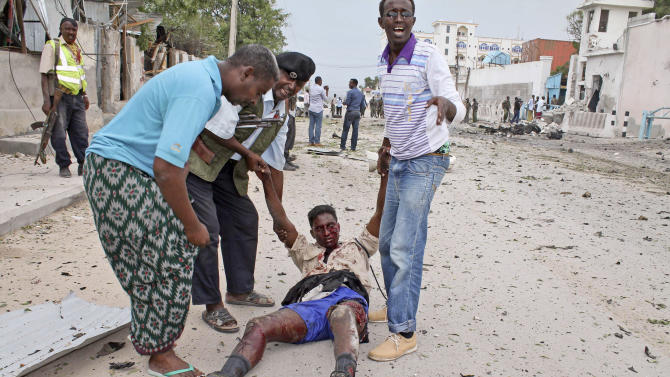 Somali men and a policeman carry a government soldier wounded during an attack on the U.N. compound in Mogadishu, Somalia Wednesday, June 19, 2013. Al-Qaida-linked militants detonated multiple bomb blasts and engaged in ongoing battles with security forces in an attempt to breach the main U.N. compound in Mogadishu, officials said Wednesday. (AP Photo/Farah Abdi Warsameh)