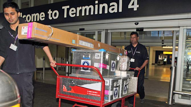 Officials help transport luggage belonging to members of the Russian Olympic team arrives at Heathrow Airport, London, Monday 16 July, 2012. Competitors are arriving in London during preparations for the upcoming London 2012 Olympic Games.  (AP Photo / Steve Parsons, PA) UNITED KINGDOM OUT - NO SALES - NO ARCHIVES