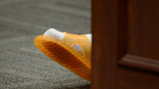 The foot of Aurora theater shooting suspect James Holmes is pictured during a court hearing in Centennial, Colo., on Tuesday, June 4, 2013.  Judge Carlos A Samour Jr. accepted  plea of not guilty by reason of insanity from Holmes.  He also ruled that prosecutors can have access to a notebook Holmes sent to a psychiatrist before last summer's rampage. (AP Photo/The Denver Post, Andy Cross, Pool)