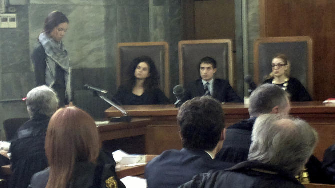 """Karima el-Mahroug, from Morocco, the woman at the center of a sex scandal involving former Italian Premier Silvio Berlusconi, is seen in the witness stand at left as she testifies for the first time in the trial of three Berlusconi aides charged with recruiting her and other women for prostitution, in Milan's courthouse, Italy, Friday, May 17, 2013. El-Mahroug, known by the nickname Ruby Heart Stealer, has made carefully orchestrated statements to the media since the scandal broke but has never publicly given sworn testimony. Both she and Berlusconi deny having had sex. Prosecutors in Berlusconi's separate trial on charges of paying for sex with a minor and trying to cover it up say her testimony is unreliable and are relying on her sworn statements. Writing above judges reads in Italian """"The law is equal for all.""""(AP Photo/Luca Bruno)"""