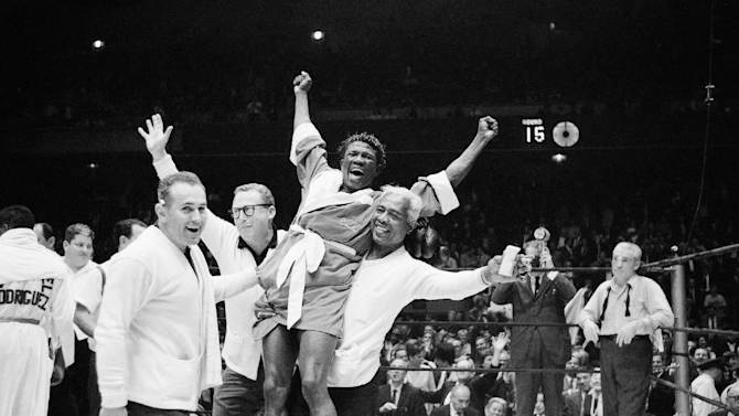 FILE - In this June 8, 1963 file photo, Emile Griffith is hoisted by handlers after a split decision victory over Luis Rodriguez, for the welterweight world championship at New York's Madison Square Garden. The International Boxing Hall of Fame says Griffith has died. He was 75. The hall said Tuesday, July 23, 2013, he died at an extended care facility in Hempstead, N.Y. (AP Photo, File)