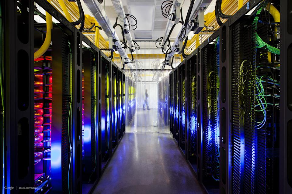 This undated photo made available by Google shows the campus-network room at a data center in Council Bluffs, Iowa. Routers and switches allow Google's data centers to talk to each other. The fiber cables run along the yellow cable trays near the ceiling. (AP Photo/Google, Connie Zhou)
