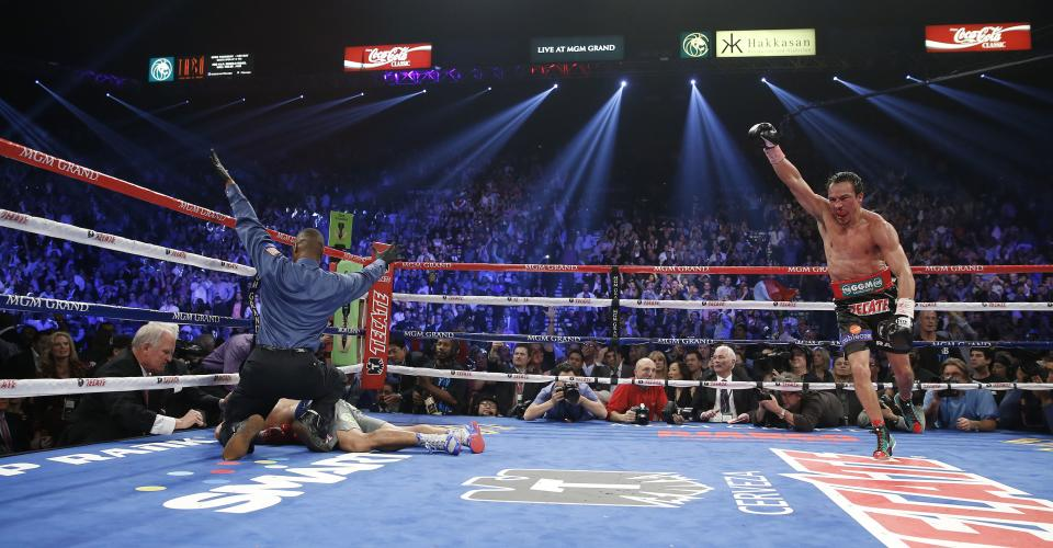 Referee Kenny Bayless, left, calls the fight as Juan Manuel Marquez, from Mexico, right, celebrates after he knocked out Manny Pacquiao, from the Philippines, lower left, in the sixth round of their WBO world welterweight  fight Saturday, Dec. 8, 2012, in Las Vegas. (AP Photo/Eric Jamison)