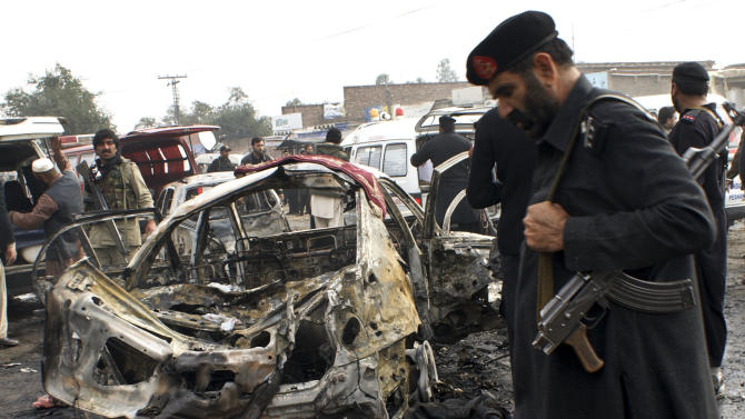 Pakistani security personnel visit the site of bombing in Pakistani tribal area of Khyber, Monday, Dec. 17, 2012. A car bomb exploded outside the women's waiting area of a government office in Pakistan's troubled northwest tribal region, killing at least many  people and wounding others, government officials said. (AP Photo/Qazi Rauf)