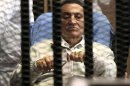 File picture shows Egypt's ousted President Mubarak sitting inside a dock at the police academy on the outskirts of Cairo