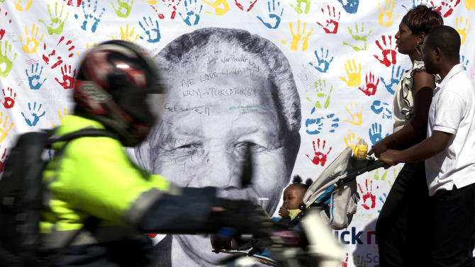 A couple walks in front of a well wisher's large banner of Nelson Mandela outside the Mediclinic Heart Hospital where former South African President Nelson Mandela is being treated in Pretoria, South Africa Friday, July 19, 2013. Hospital visitors say Nelson Mandela smiled and nodded Thursday - his 95th birthday - and South Africans celebrated upbeat reports about the former president's health after weeks of worrying that he was on the verge of death. (AP Photo/Themba Hadebe)