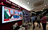 People watch a televised speech by Indian Premier Manmohan Singh in New Delhi. While political opponents accused Singh of selling out the country to foreign interests, the media lauded him for addressing the difficulties facing Asia&#39;s third-largest economy