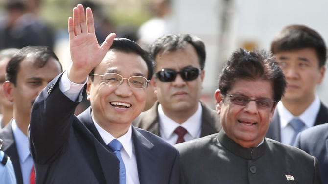 Chinese Premier Li Keqiang waves as he is received by Indian junior minister for external affairs, E. Ahamed, right, after he arrived in New Delhi, India, Sunday, May 19, 2013. Just weeks after a tense border standoff, China's new premier arrived in India on Sunday for his first foreign trip as the neighboring giants look to speed up efforts to settle a decades-old boundary dispute and boost economic ties. (AP Photo/Saurabh Das)