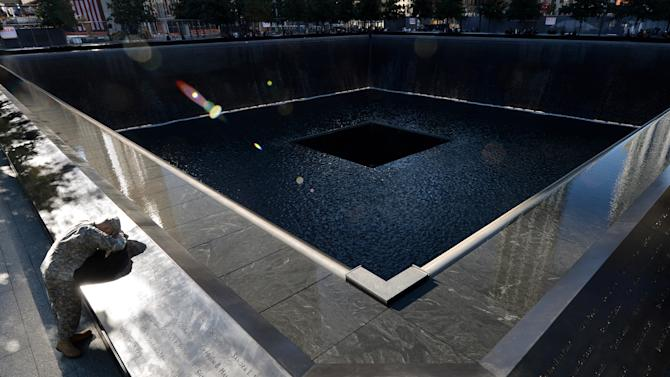 Scott Willens, who joined the United States Army three days after the attacks on Sept. 11, 2001, pauses by the South Pool of the World Trade Center Memorial during the 11th anniversary observance, Tuesday, Sept. 11, 2012 in New York. (AP Photo/Justin Lane, Pool)