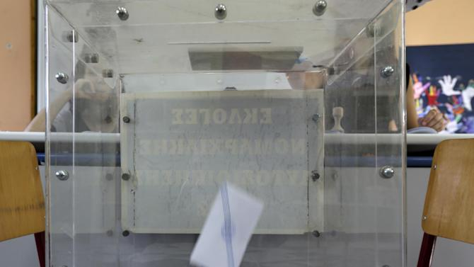 People cast their vote at a polling station in Athens, Sunday, July 5, 2015. Greeks began voting early Sunday in a closely-watched, closely-contested referendum, which the government pits as a choice over whether to defy the country's creditors and push for better repayment terms or essentially accept their terms, but which the opposition and many of the creditors paint as a choice between staying in the euro or leaving it. (AP Photo/Petr David Josek)