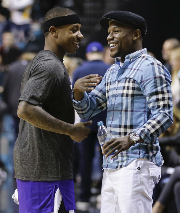 Floyd Mayweather Jr., right, talks with Sacramento Kings point guard Isaiah Thomas (22) after a preseason NBA basketball game against the Los Angeles Lakers, Thursday, Oct. 10, 2013, in Las Vegas.  Th