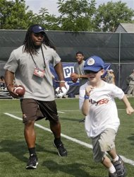 Cleveland Browns rookie running back Trent Richardson, left, gives chase during an NFL football Play 60 youth clinic at the Cleveland Browns training facility in Berea, Ohio Friday, June 29, 2012. (AP Photo/Mark Duncan)