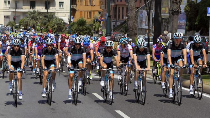 """The teammates of Wouter Weylandt  pedal at the Giro d'Italia, Tour of Italy cycling race, in Livorno, Italy, Tuesday, May 10, 2011, during a fourth stage honoring the Leopard-Trek cyclist who died in a high-speed crash. The Leopard-Trek team will continue to ride in the Giro d'Italia despite the death of cyclist Wouter Weylandt. The 26-year-old Belgian crashed Monday during a descent after clipping a wall during the third stage of the race and died at the scene despite medical staff trying to revive him for 40 minutes. """"We will start out of respect for the family of Weylandt and also to share our grief with the world of cycling,"""" Leopard Trek general manager Brian Nygaard said Tuesday. (AP Photo/Alessandro Trovati)"""