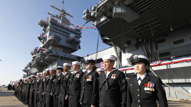 The crew of the USS Enterprise stands at attention after disembarking the ship during the inactivation ceremony for the first nuclear powered aircraft carrier USS Enterprise at Naval Station Norfolk  Saturday, Dec. 1, 2012 in Norfolk, Va.   The ship served in the fleet for 51 years.  (AP Photo/Steve Helber)
