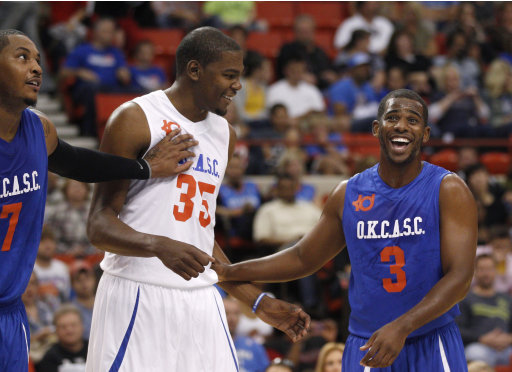 Chris Paul, right, jokes with Kevin Durant, center, on the foul line, in a charity basketball invitational game in Oklahoma City, Sunday, Oct. 23, 2011. Carmelo Anthony is at left. The game was the latest in a series of exhibition games across the country as NBA players stay in the spotlight while locked out by the league. (AP Photo/Sue Ogrocki)