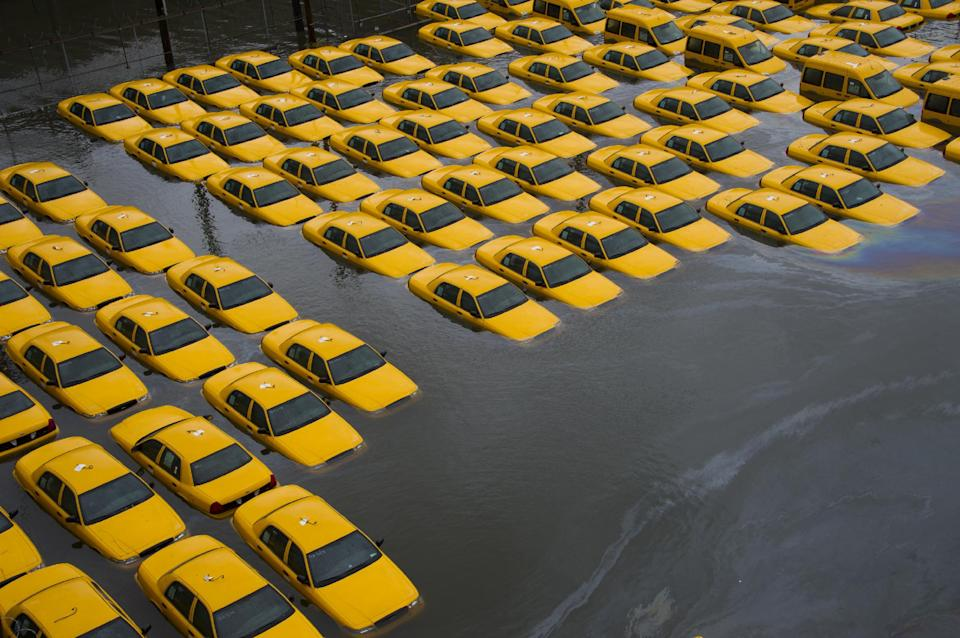 FOR USE AS DESIRED, YEAR END PHOTOS - FILE - In this Oct. 30, 2012 file photo, a parking lot full of yellow cabs is flooded as a result of superstorm Sandy in Hoboken, NJ. (AP Photo/Charles Sykes, File)