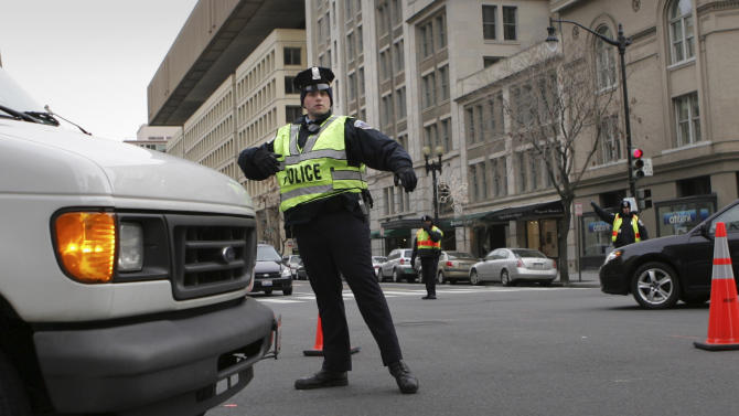 FILE - This Jan. 17, 2009 file photo shows a Washington Metropolitan police officer directing traffic  in Washington. From a transportation perspective, Inauguration Day won't be all that different from most regular workdays in the nation's capital: If you want to get downtown on time, you're probably better off not driving. Instead, the hundreds of thousands of people spilling into the city are encouraged to travel by rail, bus or bicycle. And no matter what they choose, they'll eventually end up on foot _ and possibly walking several miles _ to catch a glimpse of President Barack Obama. (AP Photo/Lawrence Jackson, File)