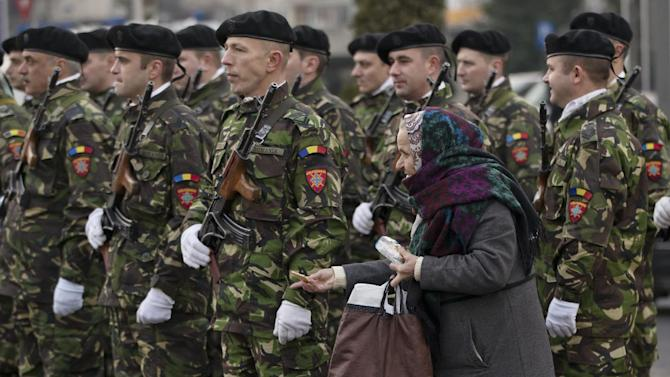 A woman offers biscuits to an honor guard of soldiers before a commemoration at the Revolution Heroes Cemetery in Bucharest ,Romania, Sunday, Dec. 21, 2014. The anti-communist uprising, which left more than thousands dead, and ended the rule of dictator Nicolae Ceausescu, who was executed, started in the western Romanian town of Timisoara on Dec. 16, 1989 and in Bucharest, Romania's capital on Dec. 21, 1989.(AP Photo/Vadim Ghirda)