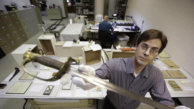 """Senior curator for the Museum of the Confederacy, Robert Hancock, holds the sword carries by Confederate Brigadier General Lewis A. Armistead during the Battle of Gettysburg in a work room at the museum in Richmond, Va., Wednesday, May 1, 2013. The Museum of the Confederacy in Richmond, Va., will open the exhibit """"Gettysburg: They walked through blood"""" on May 11 to commemorate the 150th anniversary of the Battle of Gettysburg. (AP Photo/Steve Helber)"""