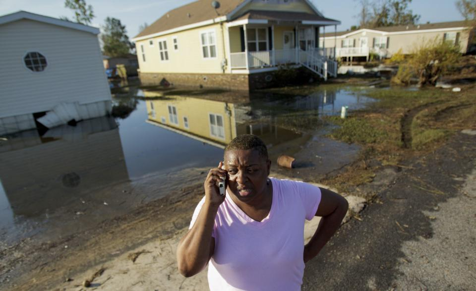 Natachia Riley talks outside the house of her mother, Clara Williams, in Ironton, La., which was flooded from Hurricane Isaac, near Louisiana Hwy 23 in Plaquemines Parish  Monday, Sept. 3, 2012. The house was built seven years ago after mother's previous home was destroyed by Hurricane Katrina. (AP Photo/Matthew Hinton)
