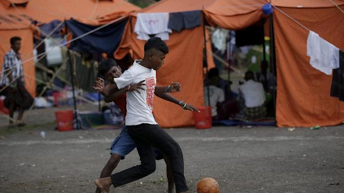 Ethnic Rohingya men play soccer at their temporary shelter in Langsa, Aceh province, Indonesia Friday, May 22, 2015. In the past three weeks, thousands of refugees and migrants have washed ashore in Malaysia, Indonesia and Thailand, according to the International Organization for Migration. Half are Rohingya and the rest are from Bangladesh, the IOM said. The U.N. refugee agency estimates more than 3,000 others may still be at sea. (AP Photo/Tatan Syuflana)