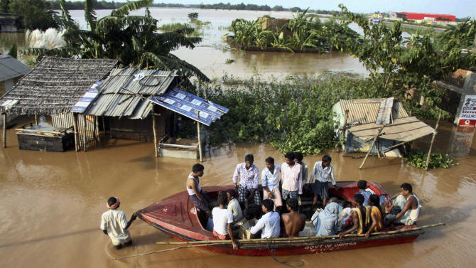 Indian villagers sit in a rescue boat in the flooded Rasulpur village in Orissa's Jajpur district, India, Monday, Sept. 26, 2011. Monsoon rains collapsed mud huts and riverbanks, flooding wide swaths of north and east India and killing at least 48 people over the weekend, officials said Monday. (AP Photo)-INDIA OUT
