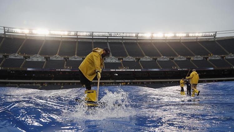 Stadium employees push rain water off the tarp at Soldier Field before an NFL football game between the Chicago Bears and Minnesota Vikings, Sunday, Sept. 15, 2013, in Chicago