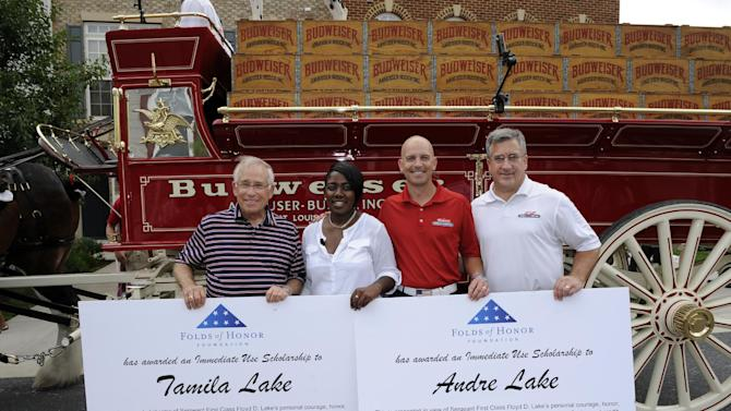 IMAGE DISTRIBUTED FOR ANHEUSER-BUSCH - Neal Katcef, left, local Anheuser-Busch wholesaler, Major Dan Rooney, second from right, of Folds of Honor Foundation, and Rocky Sickmann, right, director of military sales for Anheuser-Busch, present two Folds of Honor Scholarships to Linda Lake, second from left, Tuesday, July 2, 2013, in Laurel, Md. Since 2010, Budweiser has raised more than $5 million for the Folds of Honor Foundation to provide educational scholarships to family members of military killed or disabled in action. Lake's husband, Sergeant First Class Floyd D. Lake, died in Baghdad, Iraq, while supporting Operation Iraqi Freedom in 2007. (Nick Wass/AP Images for Anheuser-Busch)