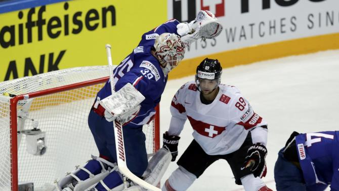 France's goaltender Huet jumps in front of Switzerland's Almond during their Ice Hockey World Championship game at the O2 arena in Prague